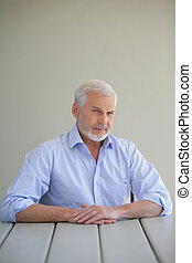 Grey haired man sitting on his patio