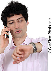 A businessman over the phone looking at his watch