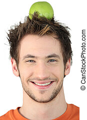 Young man with an apple on his head
