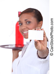 young woman with tray giving business card