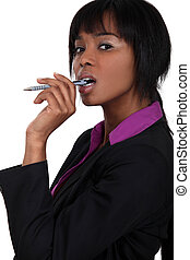 Businesswoman chewing on pen