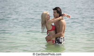 Resort romance - Sweet couple embracing in water being on...