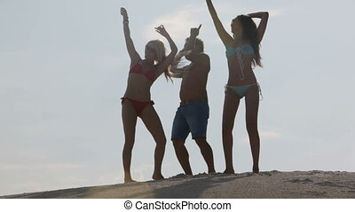 Resort party - Cheerful friends dancing on the beach in the...