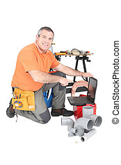 Plumber with tools and material kneeling to use a laptop...