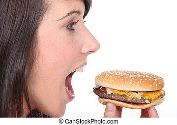 Brunette girl eating hamburger, profile-view