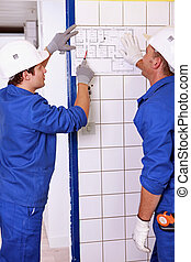 Electricians looking at a diagram