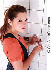 Female electrician working in a tiled room