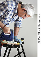 Gray-haired handyman using an electric drill