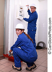 Two electrician repairing fuse box