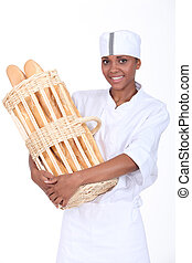 A baker holding a basket of bread
