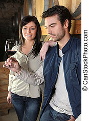 Man and woman tasting wine in cellar