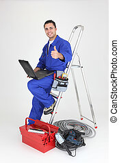 Male electrician with laptop and equipment