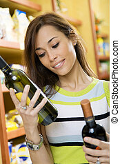 italian food - woman in a supermarket comparing two wines
