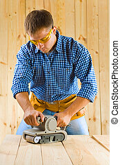 young men works with detail sander
