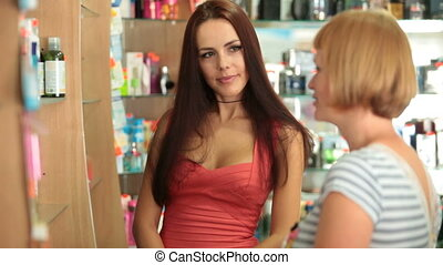 Woman Buying Cosmetics - Young woman talking with shop...