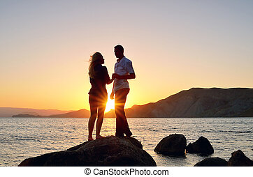 Young couple talking to a rock by the sea at the setting sun