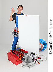 Female plumber with tools of the trade and a board left blank for your message