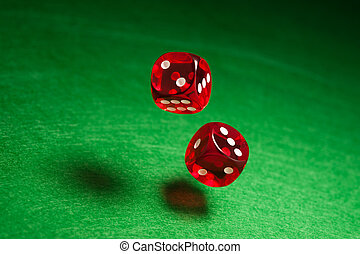 Rolling red dice over green surface