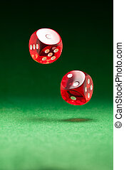 Rolling red dice on a casino table - Rolling red dice over...