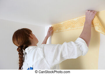 Woman putting up wallpaper