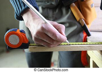Carpenter marking a piece of wood