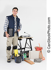 young tiler standing amid tools