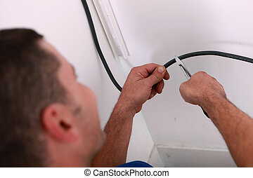 Man cutting black electrical wire