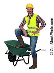 Man casually stood by empty wheelbarrow