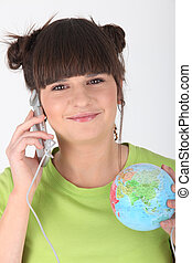 Woman making telephone call and holding globe