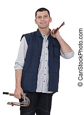 portrait of plumber holding copper pipes