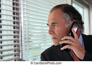 Senior businessman looking through blinds whilst making call