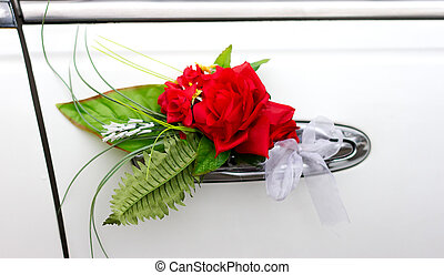 Red flower on the handle of a wedding car