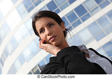 Young businesswoman using a cellphone outside an office building