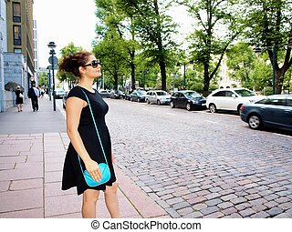 Beautiful brunet, black dress, waiting on the sidewalk