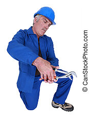 Man using a spanner on empty copyspace