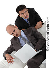 Two businessmen by sofa