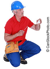 Tradesman holding a plug and a screwdriver