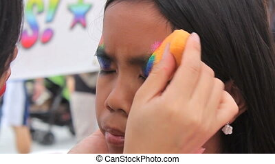 Girl Getting Rainbow Face Painting - A cute little 10 year...