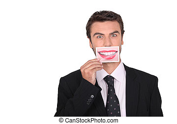 Man holding a photograph of a womans smile over his mouth