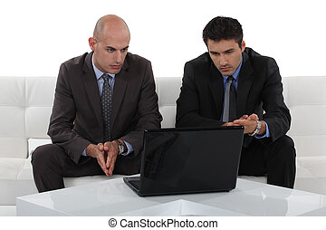 two businessmen sitting on a sofa and watching something on...