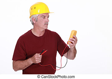 Tradesman looking at his multimeter's display