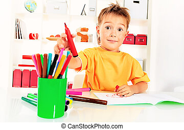 studing - Little boy drawing in his notebook at home.