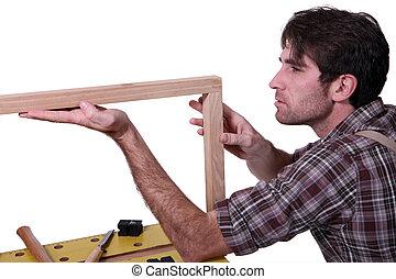 Joiner inspecting wooden frame