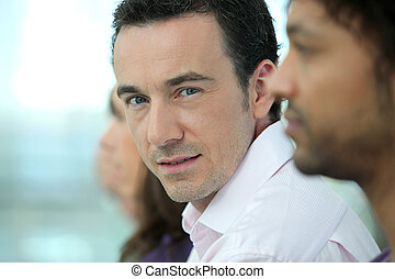 Headshot of a handsome man standing with colleagues in a...