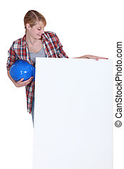 Tradeswoman looking at a blank sign with interest