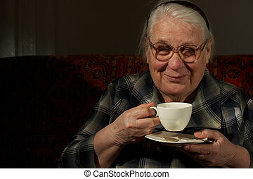 The darling old woman with favourite drink - The sitting old...