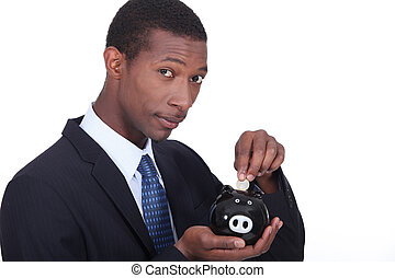 Man putting coins in piggy bank