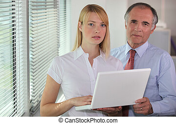 Businessman and his assistant looking at a laptop