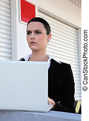 serious-looking brunette outdoors with laptop