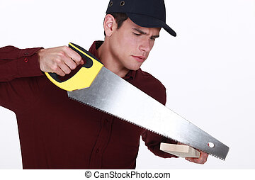 Man using a saw to cut a wooden plank